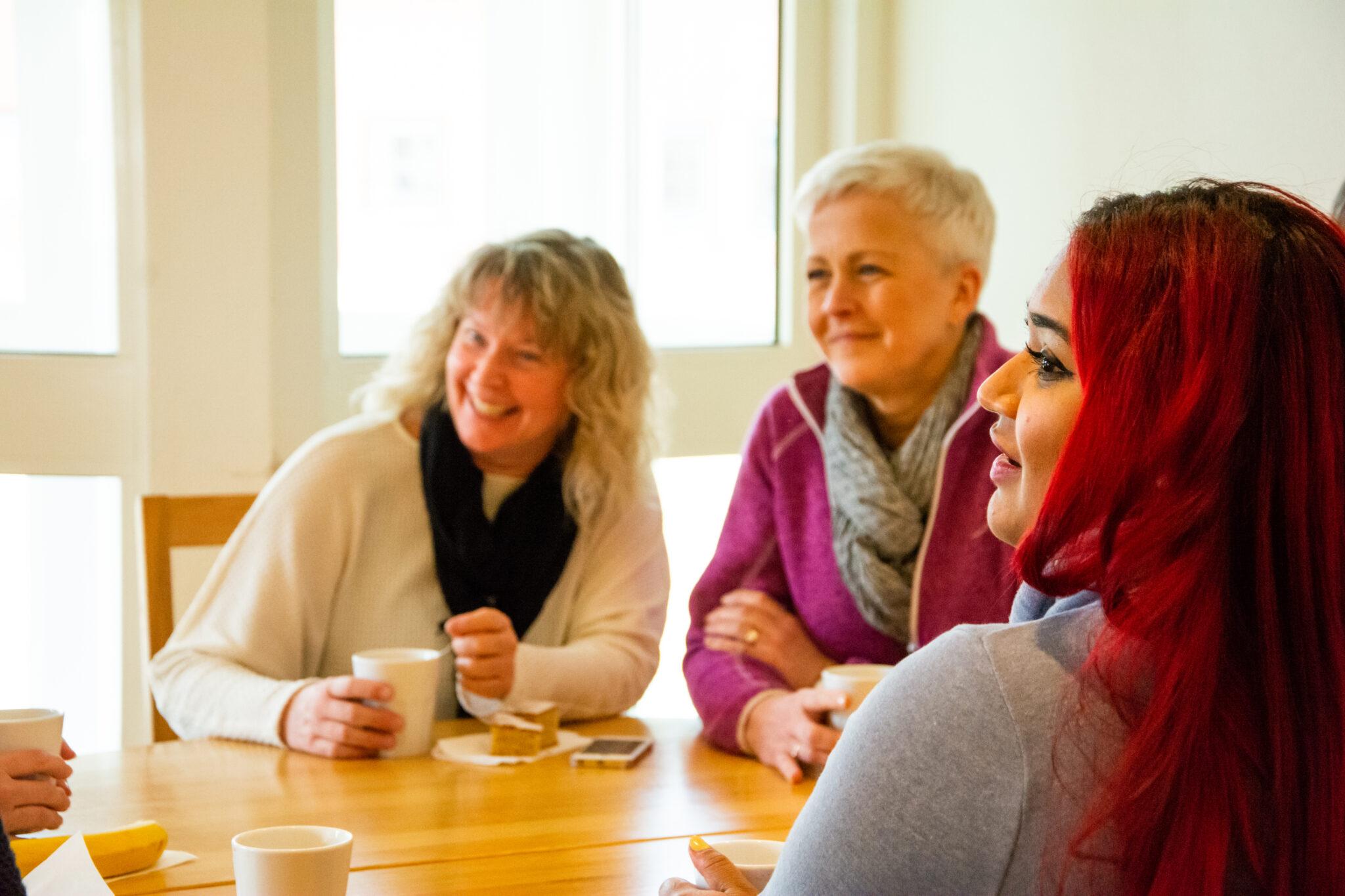 Diakoner skrattar, pratar och diskuterar vid ett bord